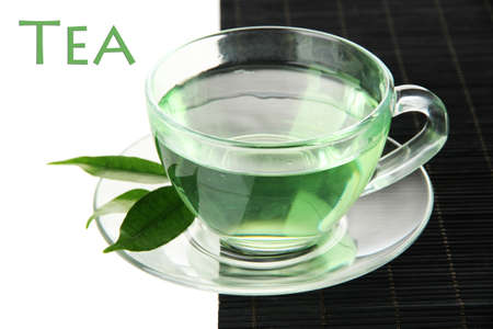 Transparent cup of green tea on bamboo mat, isolated on white photo