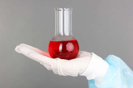 Glass tube with fluid in scientist hand during medical test on grey background photo