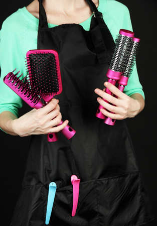 Hairdresser in uniform with working tools, isolated on black photo
