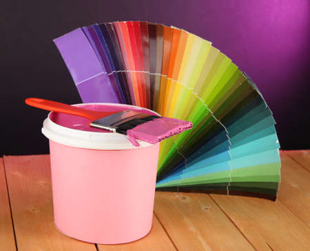 refurbishing: Paint pot, paintbrush and coloured swatches on wooden table on dark purple background Stock Photo