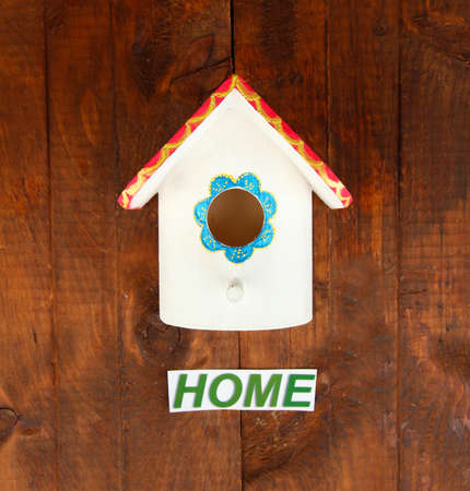 Decorative nesting box and sign on wooden background photo