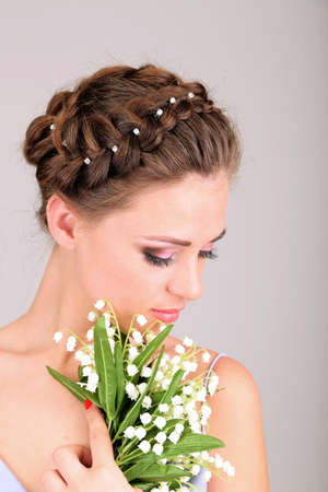 Young woman with beautiful hairstyle and flowers, on grey background photo
