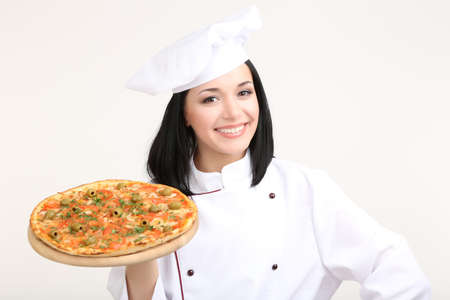 Beautiful girl chief-cooker with pizza isolated on white photo