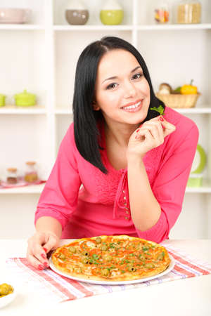 Beautiful girl with delicious pizza on kitchen background photo