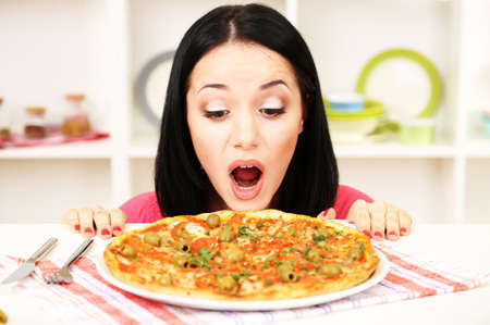 Beautiful girl wants to eat delicious pizza on kitchen background photo