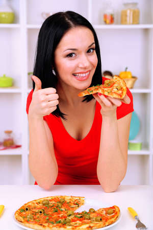 Girl with delicious pizza on kitchen background photo