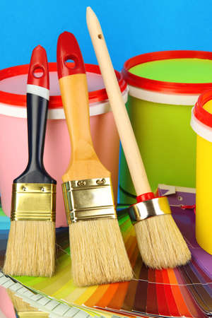 refurbishing: Set for painting: paint pots, brushes, palette of colors on blue background Stock Photo