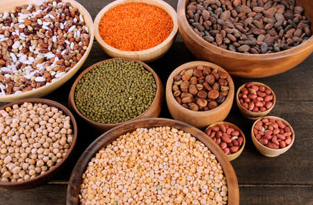 Different kinds of beans in bowls on  table close-up photo