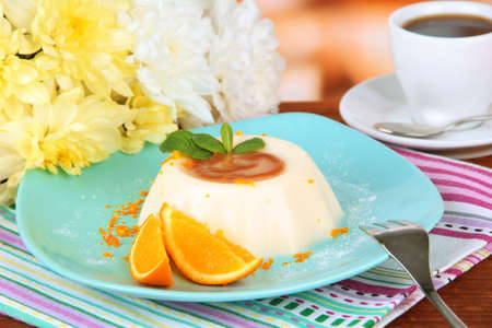 Panna Cotta with orange zest and caramel sauce, on color wooden background photo