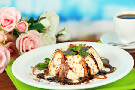 Panna Cotta with chocolate  and caramel sauces, on bright background photo