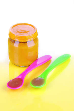 Baby food with weaning spoons on yellow background photo