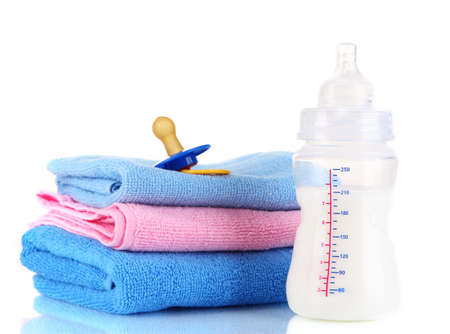 Bottle for milk with towels and nipple isolated on white photo