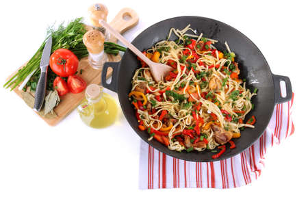 Noodles with vegetables on wok isolated on white photo
