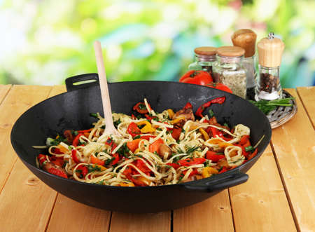 wok: Noodles with vegetables on wok on nature background background