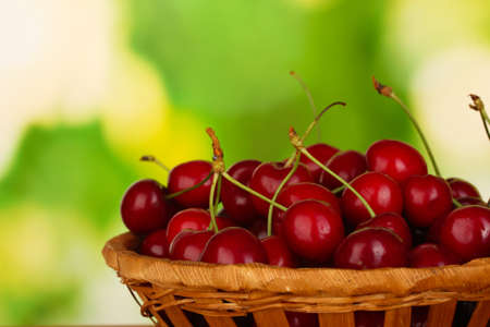 cherry in wicker bowl on wooden table on green background close-up photo