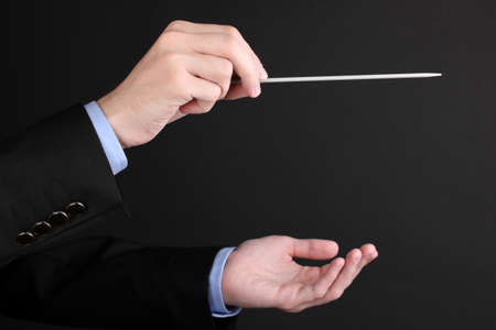 opera: Music conductor hands with baton isolated on black