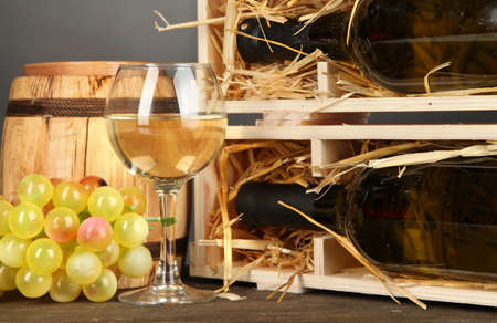 Wooden case with wine bottle, barrel, wineglass and grape on wooden table on grey background photo