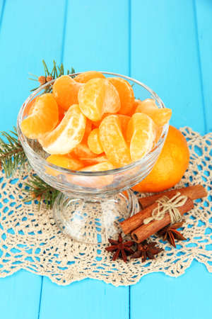 Tasty mandarine's slices in glass bowl on blue background photo