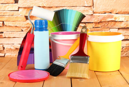 Paint pots, paintbrushes and coloured swatches on wooden table on stone wall background photo