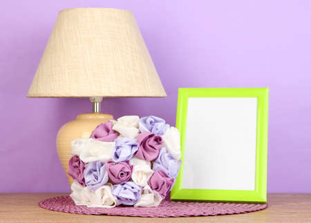 Colorful photo frame, lamp and flowers on wooden table on lilac background