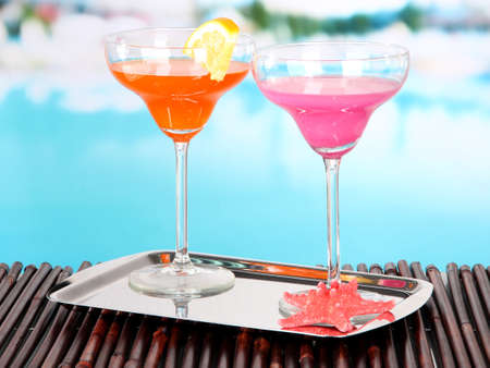 party tray: Glasses of cocktails on table near pool