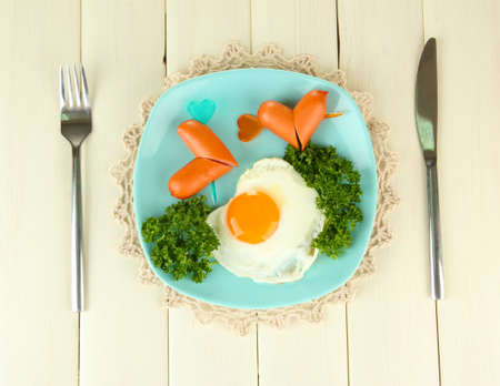 scrambled: Sausages in form of hearts, scrambled eggs and parsley, on color plate, on wooden background