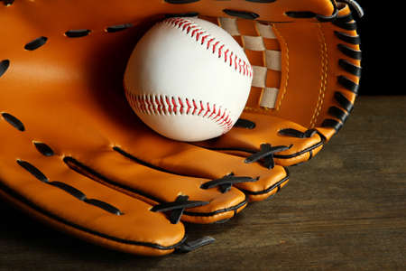 Baseball glove and ball on dark background photo