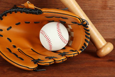 Baseball glove, bat and ball on wooden background photo