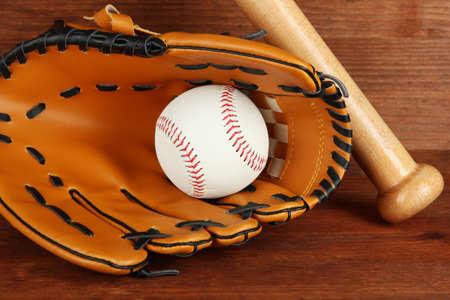Baseball glove, bat and ball on wooden background