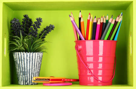Colorful pencils in pail on shelf on pink background photo