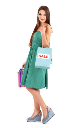 Young beautiful girl in green dress holding bright  shopping bags, isolated on white photo