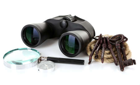 Black modern binoculars with magnifying glass, compass and old keys isolated on white photo