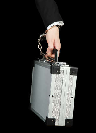 Hand with handcuff and suitcase, isolated on black photo