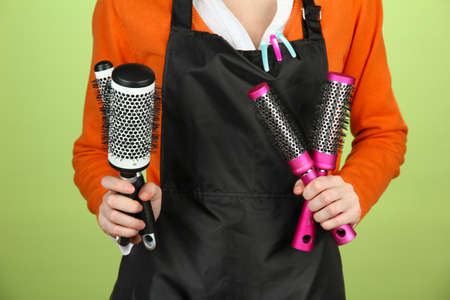 uniform curls: Hairdresser in uniform with working tools, on color background