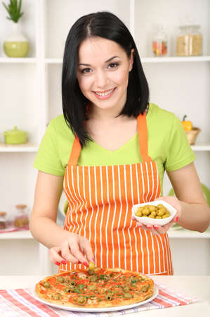 Girl housewife with delicious pizza on kitchen background photo
