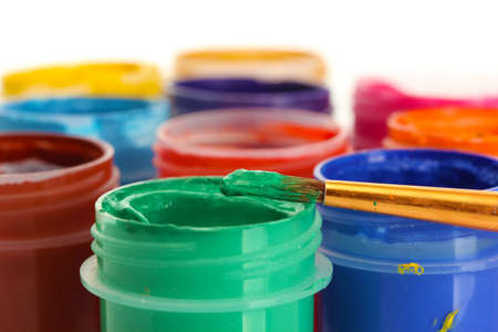 jars with multicolored gouache on white background close-up