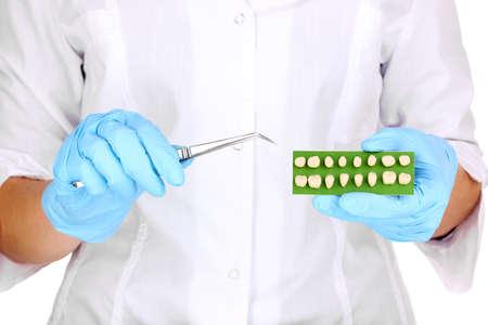 Dentists hands with denture and dental tweezers photo
