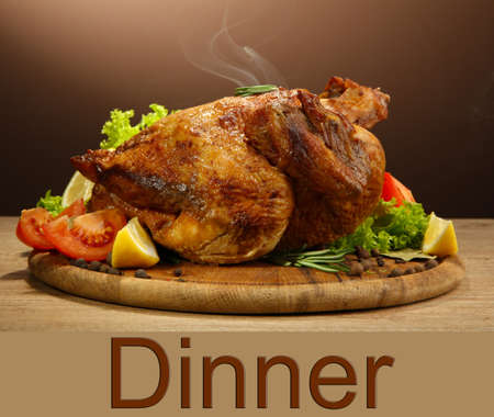 Whole roasted chicken with vegetables, on wooden table, on brown background photo