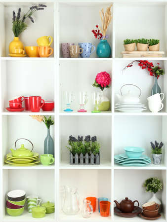 wooden furniture: Beautiful white shelves with tableware and decor  Stock Photo