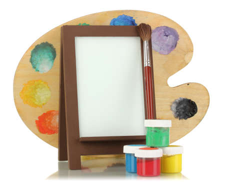 Photo frame as easel with artist's tools isolated on white photo