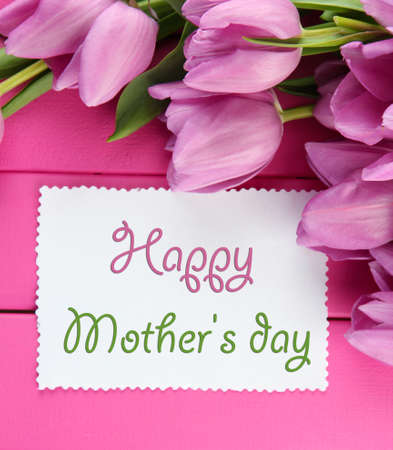mothers group: Beautiful bouquet of purple tulips and blank card on pink wooden background