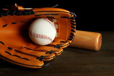 Baseball glove, bat and ball on dark background photo