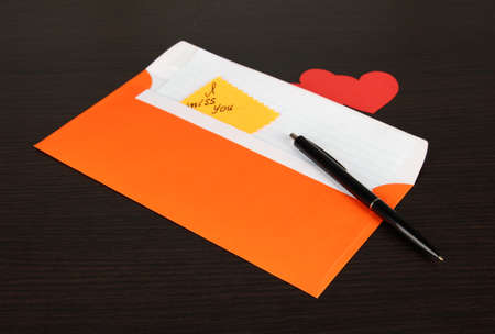 Note in envelope with pen on wooden background photo