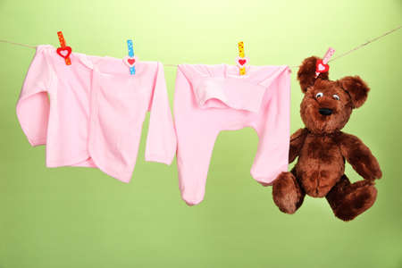 woman hanging toy: Baby clothes hanging on clothesline, on color background Stock Photo