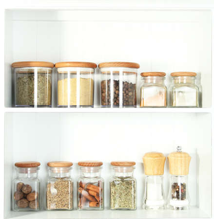 Beautiful white shelves with spices in glass bottles photo