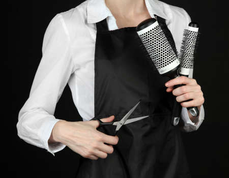 uniform curls: Hairdresser in uniform with working tools, isolated on black