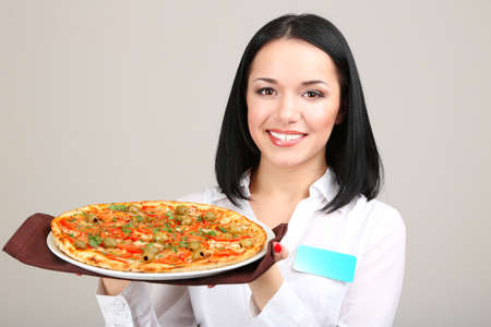 Beautiful girl waiter with pizza isolated on white photo