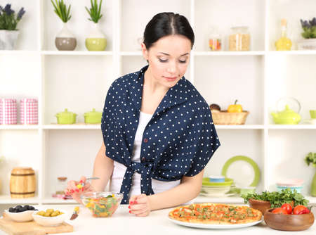 quick snack: Pretty girl selects pizza or diet on kitchen background