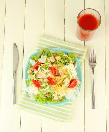 ensalada cesar: Ensalada C?sar en el plato azul, sobre fondo de madera de color Foto de archivo