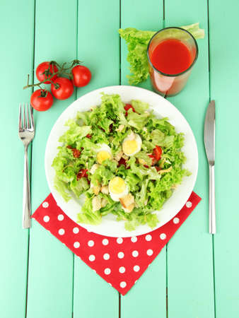 Caesar salad on blue plate, on color wooden background photo